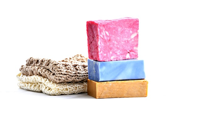 Stack of 3 handmade bars of soaps with with 2 folded knitted washclothes