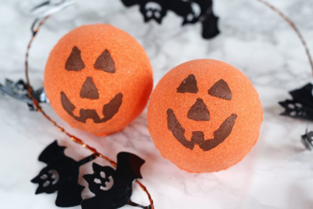 This is a cute Halloween DIY idea - Jack-o'-lantern bath bomb recipe scented with essential oils. They make for a fun kids craft, homemade gift or decoration. #halloween #bathbomb #kidcraft #diy #pumpkin