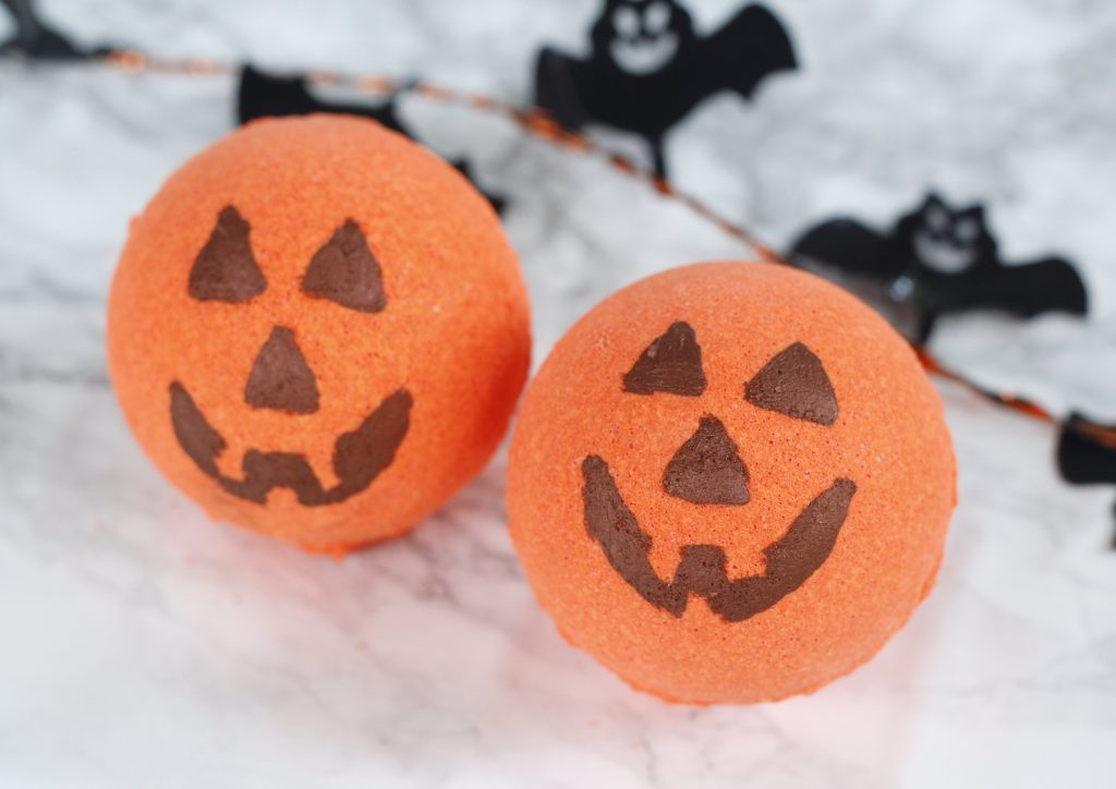 This is a cute Halloween DIY idea - Jack-o'-lantern bath bombs recipe scented with essential oils. They make for a fun kids craft, homemade gift, decoration or no candy treat. #halloween #bathbomb #kidcraft #diy #pumpkin