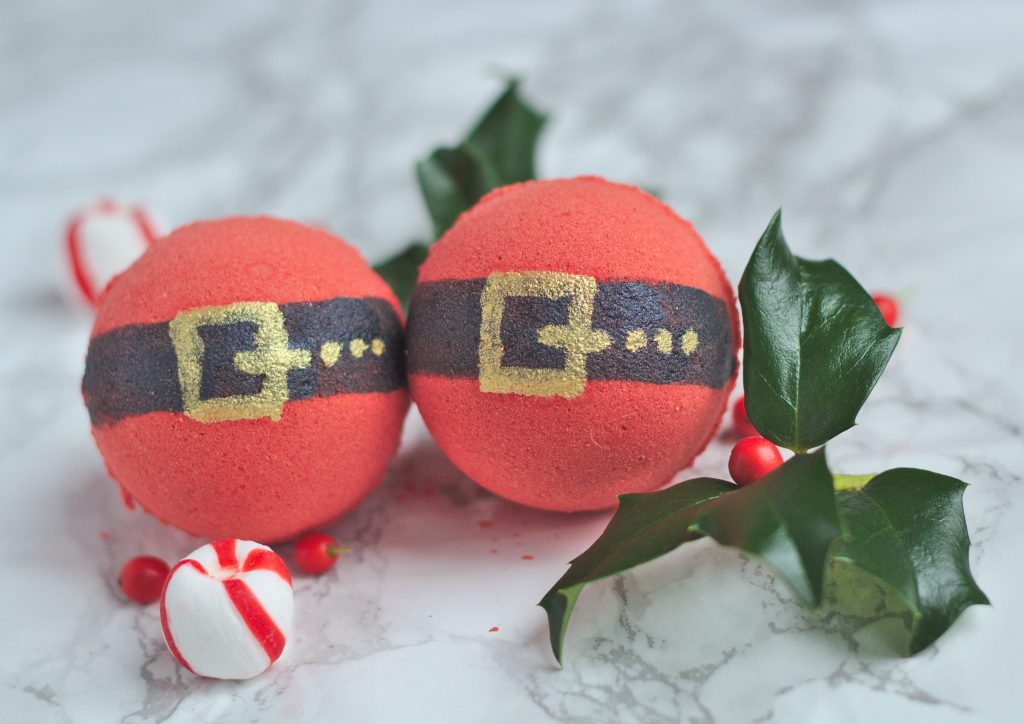two red bath bombs with santa belts painted on