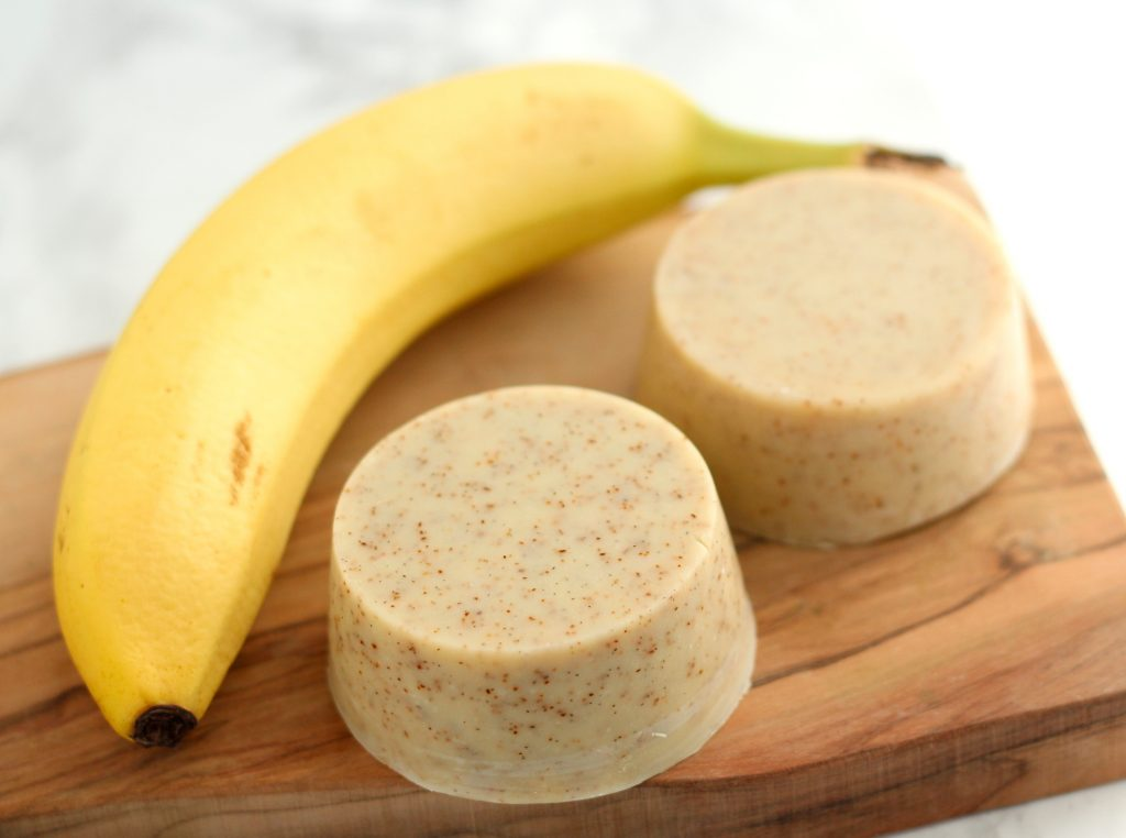 Ripe banana with two round soaps