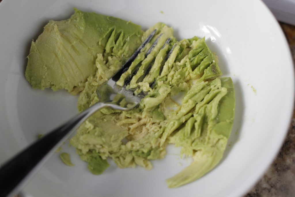 smashing avocado with fork
