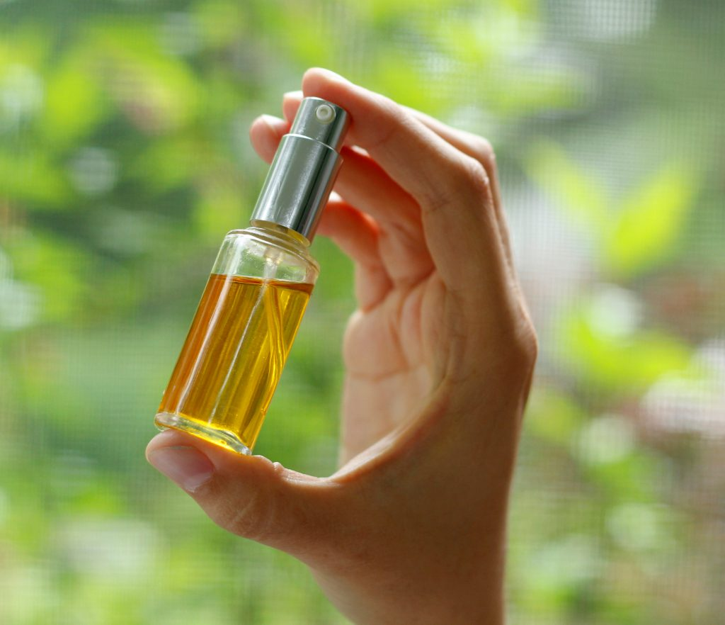 hand holding face oil serum in a bottle
