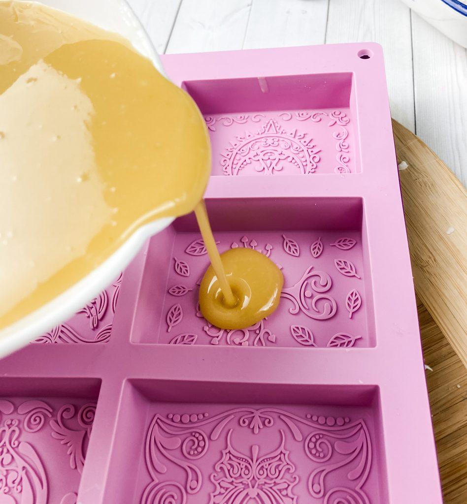 pour handmade cold process goat milk soap into molds